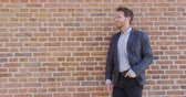 brasão : Confident business entrepreneur man young businessman looking to the side portrait against city office brick wall background. Smiling caucasian male professional in smart casual jacket. Stock Footage