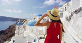 Киклады : Vacation Travel in Europe - Tourist Woman Traveling In Oia Santorini in Greece. Happy young woman looking at famous blue dome church landmark destination. Greek islands