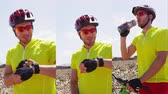 függőleges : Vertical Videos: Mountain biking man using smartwatch sport watch looking at heart rate monitor fitness tracker resting during MTB bike ride in nature drinking water.