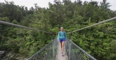 suspensão : Hiking. Woman tramping in New Zealand, Abel Tasman National Park. Young traveller backpacking crossing swing bridge over Falls River