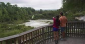 tapu : Traveling New Zealand. Tourists couple at Champagne pool at Wai-O-Tapu pools Sacred Waters. Tourist attraction Waiotapu, Rotorua, north island. Active geothermal area, Okataina Volcanic Centre, Taupo.