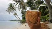 coco : Coconut water drink on paradise beach - vacation woman holding coconut. Closeup of fresh tropical coconut fruit for healthy snack during summer holidays.