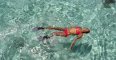 estância turística : Vacation travel - woman swimming in clear pristine water relaxing on her back wearing red bikini and pink snorkeling fins. Beautiful beach lagoon top view. Vídeos