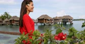 local : Travel Vacation luxury in French Polynesia Tahiti - elegant woman by overwater bungalow looking at beach and ocean wearing flower in hair. Multiracial female model. Bora Bora, French Polynesia.