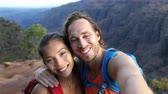 kanion : Couple taking selfie video having fun on hike on Hawaii. Woman and man in love taking candid selfportrait while on hiking travel in Waimea Canyon State Park, Kauai, Hawaii, USA.