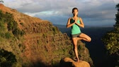 coroa : Woman doing yoga in Hawaii mountains. Asian girl meditating in tree pose with praying hands above head standing on one leg in Kauai, Hawaii, USA. girl in serene nature landscape.