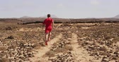 runners : Athlete running man - male runner. Sporty fit young man running fast on trail in desert training hard for fitness goals. Man running away from camera SLOW MOTION.