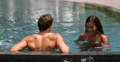 Couple relaxing together in infinity swimming pool in luxury resort spa retreat beach destination. Luxurious hotel travel vacation. People relaxed enjoying summer holidays. 59.94 FPS. Vídeos