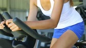 dedicado : Fit woman using exercise bike at gym. Young female is exercising at fitness gym health club.
