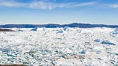 fiorde : Travel in arctic landscape nature with icebergs - Greenland tourist man explorer - tourist person looking at amazing view of Greenland icefjord - aerial video. Man by ice and iceberg in Ilulissat.