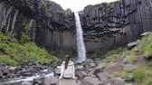 basalto : Woman enjoying majestic Svartifoss waterfall. Female is visiting famous tourist attraction of Iceland. Spectacular natural landmark on vacation in Skaftafell. Icelandic nature landscape.