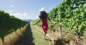 vinná réva : Wine tour. Woman in pink dress running amidst grapevines. Young cheerful female is enjoying at vineyard exploring farm on sunny day. Shot on RED in SLOW MOTION