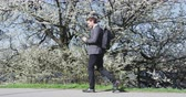 çiçekli : Smiling businessman using mobile phone by flowering tree. Male professional is walkingin city park. Business man in formalwear smart casual suit on during sunny day.