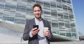 formalwear : Smiling businessman using smartphone while having coffee. Male professional on phone app holding disposable cup drinking coffee walking by office building wearing suit in city.