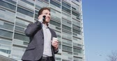 formalwear : Business People. Smiling male professional talking on smart phone while having coffee. Businessman is holding disposable cup while standing by office building wearing formals at city during sunny day.