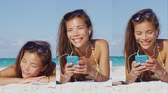banho : Vertical Video of Woman listening to music wearing earphones on beach vacation using smartphone music app on mobile phone. Girl in bikini sunbathing relaxing on beach using on in-ear headphones. Vídeos