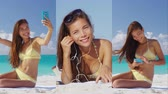 banho : Woman using smartphone app on beach taking selfie, listening to music. Vertical videos of bikini girl looking at cell phone relaxing on vacation travel. under the tropical sun.
