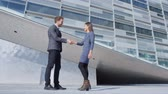 относящийся к разным культурам : Business Handshake - business people meeting shaking hands. Handshake between business man and woman outdoors by office building. Casual clothing, young people, 30s. shaking hands closeup. SLOW MOTION Стоковые видеозаписи