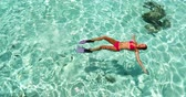 karibský : Vacation travel - woman swimming in clear pristine water relaxing on her back wearing red bikini and pink snorkeling fins. Beautiful beach reef lagoon top view.
