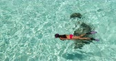 francês : Snorkeling Vacation travel woman swimming on beach clear water looking at fish wearing red bikini and pink snorkeling fins. Beautiful beach reef lagoon top view.