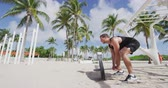 pesado : Outdoor calisthenics gym park male athlete working out on T-bar outside in summer. Man workout strength training pull up standing rowing for back muscles with heavy weights. Miam Beach, Florida, USA