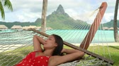 Vacation Relaxation in travel paradise. Happy smiling woman relaxing in hammock during summer holidays in tropical Bora Bora, French Polynesia, Tahiti. Luxury overwater bungalow resort hotel. Stok Video
