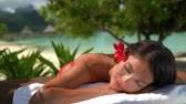 Spa Luxury Woman relaxing getting massage at hotel resort. Beauty girl lying down sleeping on towel, hibicus flowers outside. Serene ethnic woman relaxing. Mixed race Asian  Caucasian model outdoor Stok Video