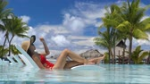 Travel luxury hotel swimming pool woman relaxing in lounging chair enjoying summer vacation. Tourist with hat and red swimsuit in water lounger. Stok Video