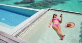 hamak : Luxury resort vacation tourist woman relaxing on overwater catamaran net bed in private bungalow suite using phone taking pictures of summer holiday high end hotel.