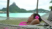 Luxury resort beach holiday woman relaxing lying down in hammock by the overwater bungalows of hotel in Bora Bora, Tahiti, French Polynesia. Happy summer vacation getaway.