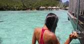 Travel luxury bikini woman taking an outdoor shower at luxury resort hotel overwater bungalow on travel in Tahiti. Vacation in paradise. Multiracial girl showering after swimming lagoon. 59.94 FPS.