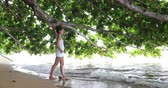 Woman at beach walking on beach covering under trees from rain - cute multiracial millennial on travel vacation on Puu Poa beach, Hanalei Bay, Kauai, Hawaii, USA. 59.94 FPS slow motion.