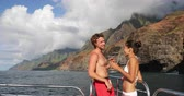 Travel couple on Hawaii cruise ship boat. Tourists People on Na Pali Coast of Kauai, Hawaii Tourist Couple looking at in NaPali, a famous Hawaiian travel destination while laughing having fun. 動画素材