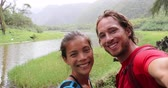 Couple taking selfie video smiling happy having fun in the rain on travel on Hawaii. Big Island black sand beach beach and hike in Pololu Valley - couple hike 動画素材