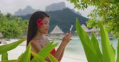 Таити : Asian beauty woman using phone in bikini on tropical beach. Beautiful youing woman on vacation and travel using smartphone app. Shot on RED in SLOW MOTION.