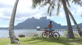polinesia francese : Woman on electric bike aka eBike on travel tourist tour on Bora Bora in French Polynesia, Tahiti. Filmati Stock
