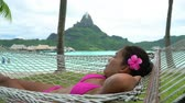 polinesia francese : Beach vacation Luxury resort holiday woman relaxing lying down in hammock by the overwater bungalows of hotel in Bora Bora, Tahiti, French Polynesia. Happy summer vacation getaway.