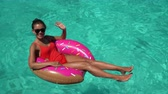 polinesia francese : Beach summer vacation happy holiday girl floating relaxing on inflatable fun donut pool float in ocean turquoise Caribbean water swimming in tropical travel destination.