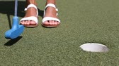 miniatűr : Mini golf or Miniature golf, also known as minigolf, mini-putt, crazy  golf. - woman putting with golf club ball in hole.