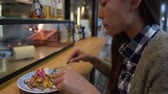 copenhague : Woman eating at danish restaurant the traditional smorrebrod open sandwich at market stall counter. Happy Asian tourist trying typical meal from Denmark. Copenhagen city travel lifestyle.
