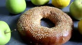 One fresh bagel with sesame seeds. Nearby are fruits - apples and lemons. On a vintage background. Delicious and healthy breakfast.