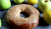 бублик : One fresh bagel with sesame seeds. Nearby are fruits - apples and lemons. On a vintage background. Delicious and healthy breakfast.