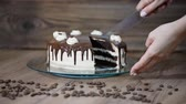 coffee cherries : Chef cutting chocolate cake. Slicing chocolate cake. Man hands slicing cake on wooden table.