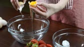 recipe : Woman hands breaking an egg to a separate egg white and yolks