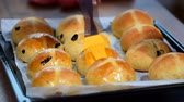 rozinky : Homemade Easter traditional hot cross buns. Female hands cover with syrup.