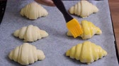 yemek tarifi : Spreading of egg yolk on croissants, closeup