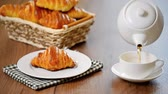 pouring drink : Pouring tea into a cup of tea. Breakfast with croissants