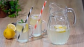 mason jar : Two mason jar glasses of homemade lemonade on a wooden background Stock Footage