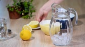 chef quipe : Preparation of lemonade from lemon and mint in a glass bottle in a light kitchen.