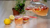 citrus fruit recipe : Woman pouring delicious strawberry lemonade into glass.